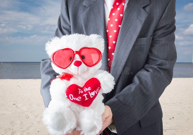Torse d'un mâle dans le costume tenant un ours de nounours blanc avec le coeur rouge photos stock