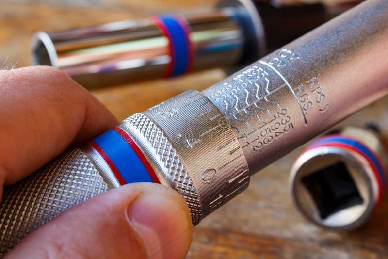Torsiemoersleutel het aanpassen door werktuigkundige in de workshop stock afbeelding
