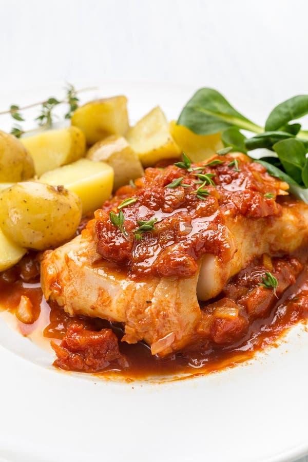 Torsk eller lyrtorsk som lagas mat i tomat- och timjansås arkivbilder