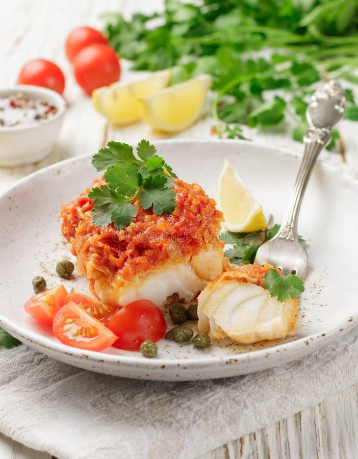 Torsk för vit fisk, lyrtorsk, nototenia, kummel som bräseras med lökar, morötter och tomater royaltyfri foto