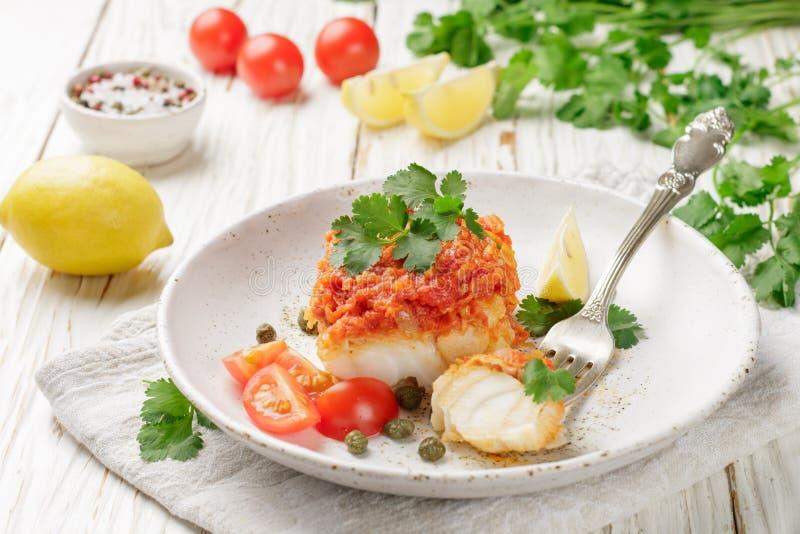 Torsk för vit fisk, lyrtorsk, nototenia, kummel som bräseras med lökar, morötter och tomater arkivbild