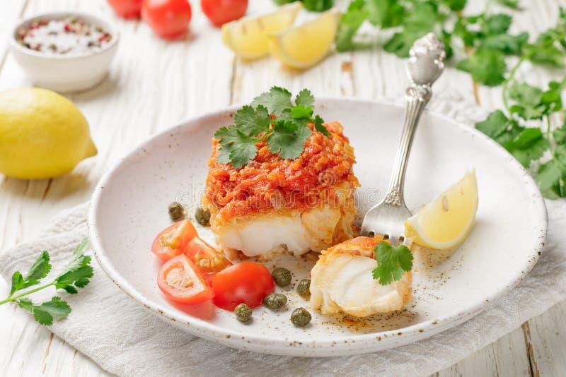 Torsk för vit fisk, lyrtorsk, nototenia, kummel som bräseras med lökar, morötter och tomater arkivfoton