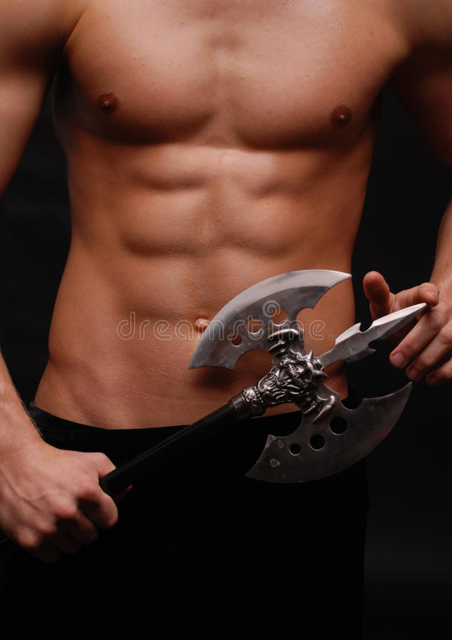 Torso with an axe. Torso with strong abs abd an axe on foreground royalty free stock photography