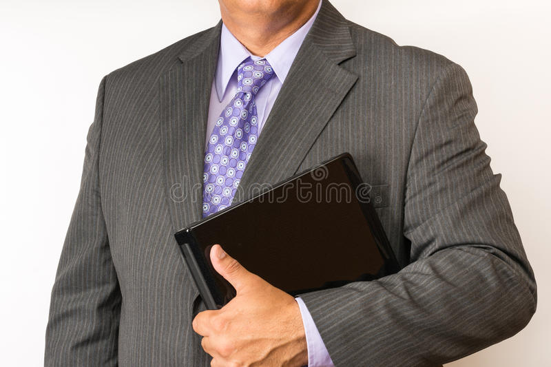 Torso of a business man wearing a suit. Elegant business person wearing a neat suit and tie holding a laptop. Business man torso. Person holding a laptop in the royalty free stock photography