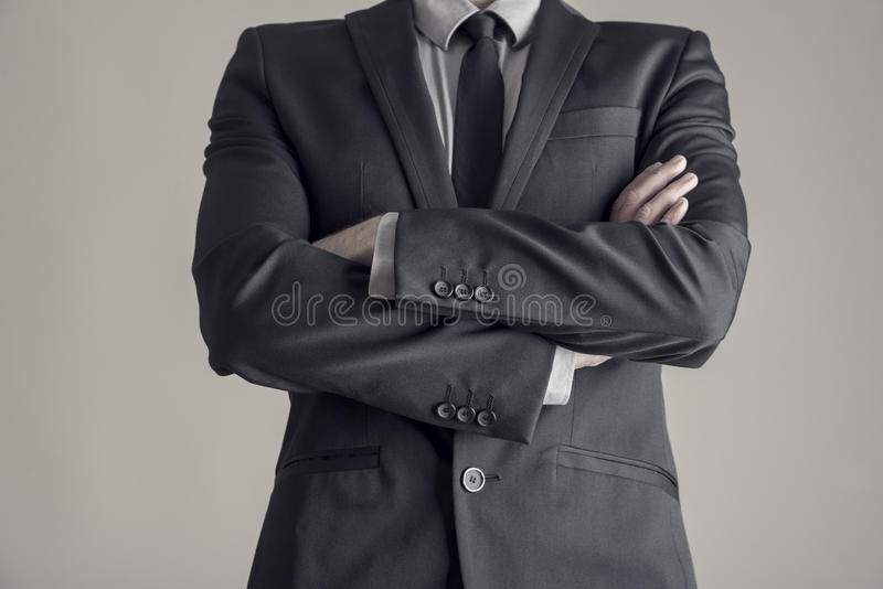 Torso of a businessman standing with folded arms royalty free stock image