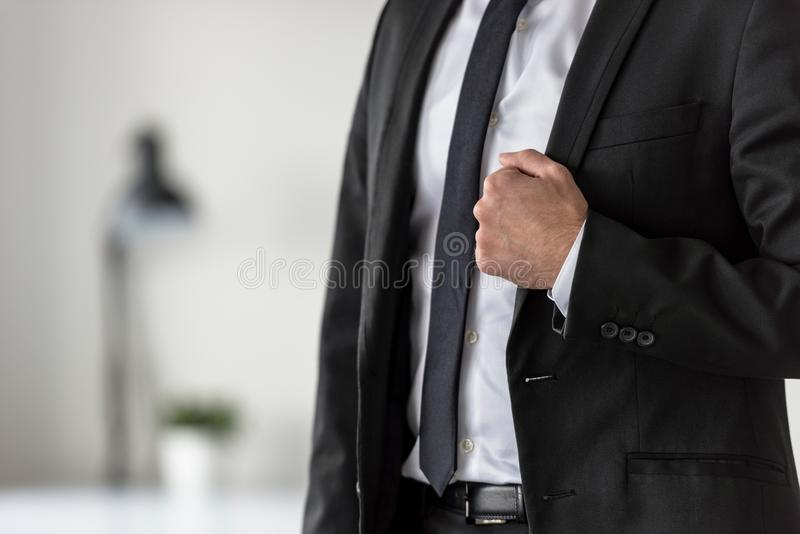 Torso of a businessman in a suit holding the lapel of his stylish jacket stock photo