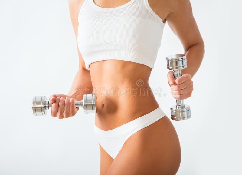 Torso de las pesas de gimnasia de elevación de una mujer joven del ajuste fotografía de archivo libre de regalías