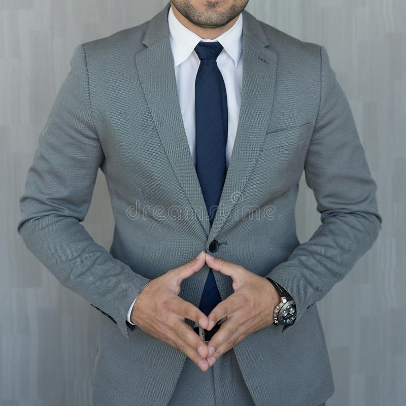 Torso dell'uomo d'affari anonimo che sta con le mani in campanile abbassato che indossa bello vestito grigio classico alla moda fotografia stock libera da diritti