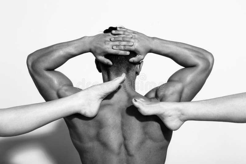 Torso dell'uomo muscolare con le mani sollevate e le gambe femminili immagini stock