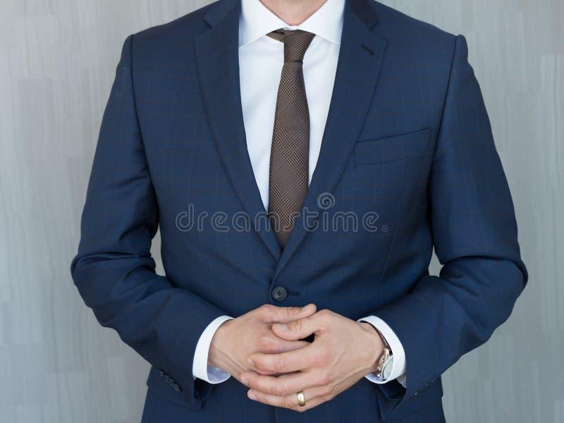 Torso di un uomo d'affari che sta con le mani serrate nella posizione media in un vestito classico dei blu navy immagini stock