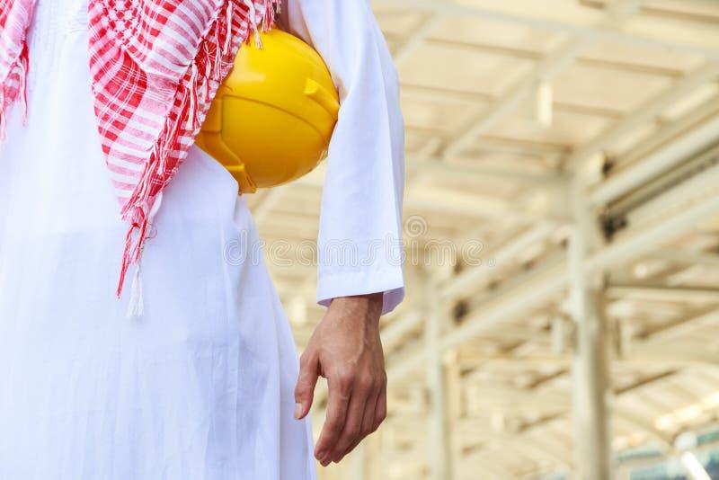 Torso do capacete amarelo disponivel árabe da posse do coordenador ou do trabalhador fotos de stock