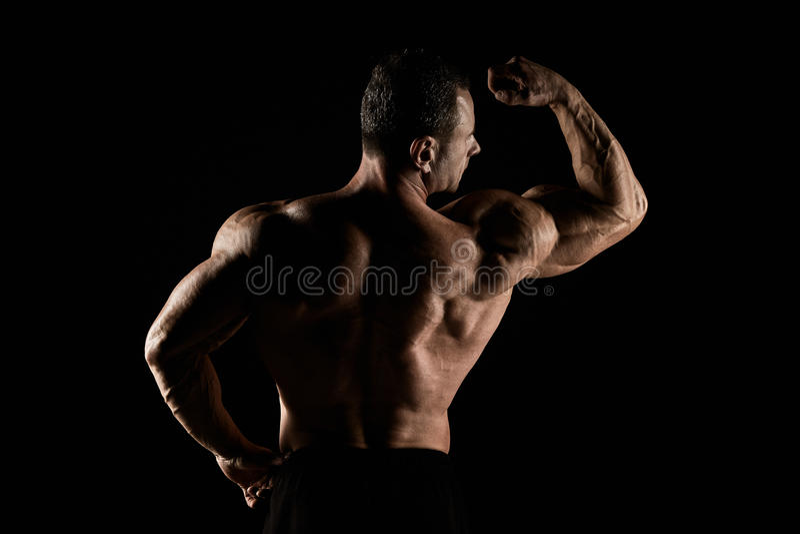 Torso do construtor de corpo masculino atrativo no fundo preto fotos de stock royalty free