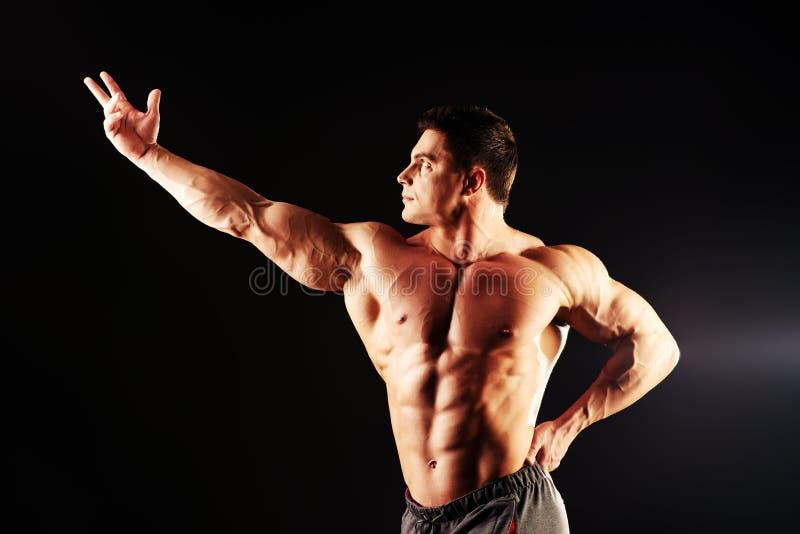 Torso man. Handsome muscular bodybuilder posing over black background stock photos