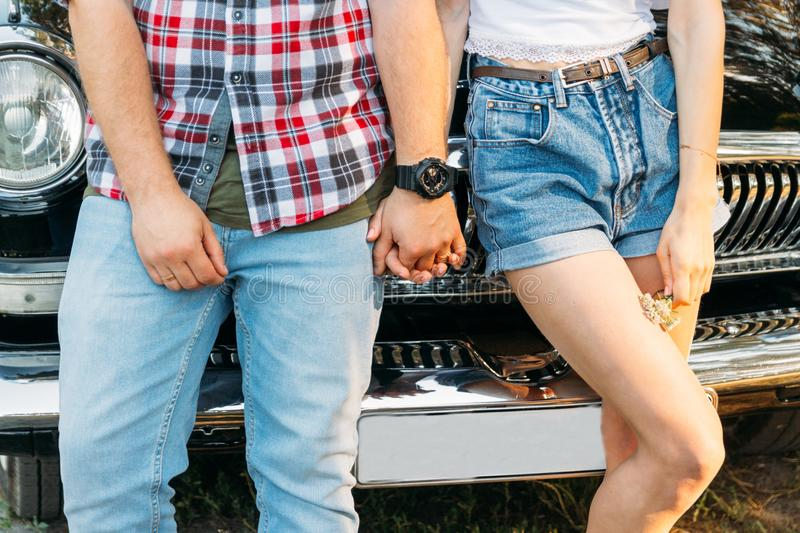 Torso of a pair that is leaning on the car and holding hands in the summer. in the hands of a flower girl, on the hand of a guy we. Aring a black watch. date in stock photography