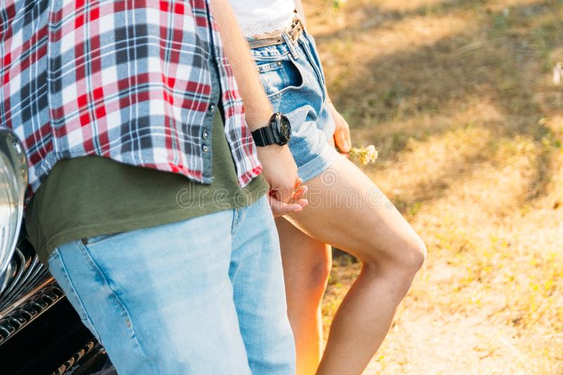 Torso of a pair that is leaning on the car and holding hands in the summer. in the hands of a flower girl, on the hand of a guy we. Aring a black watch. date in stock images