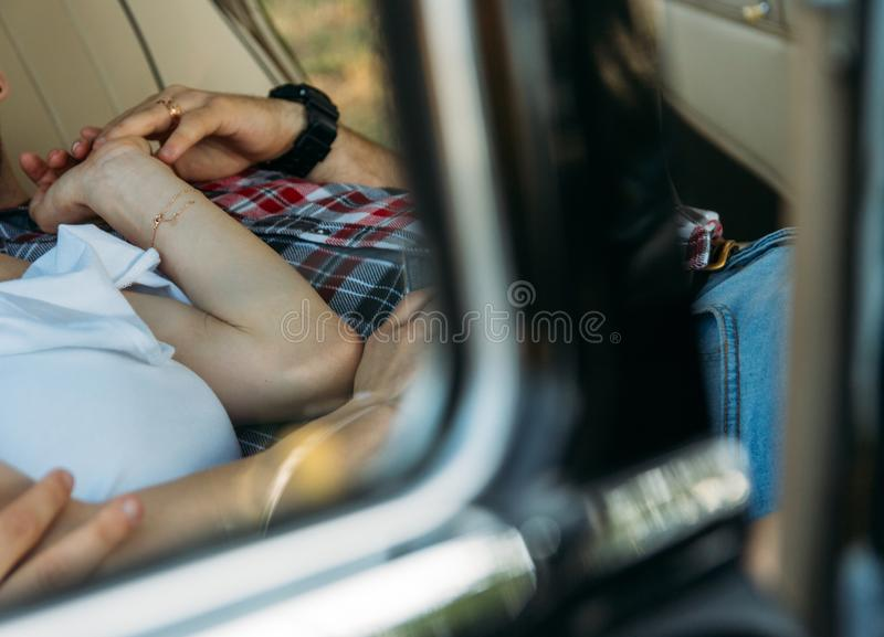 Torso of people who are lying in the car and holding hands. on his hand a watch and a gold chain, a ring. pry. look through the wi. Torso of people who are lying royalty free stock image