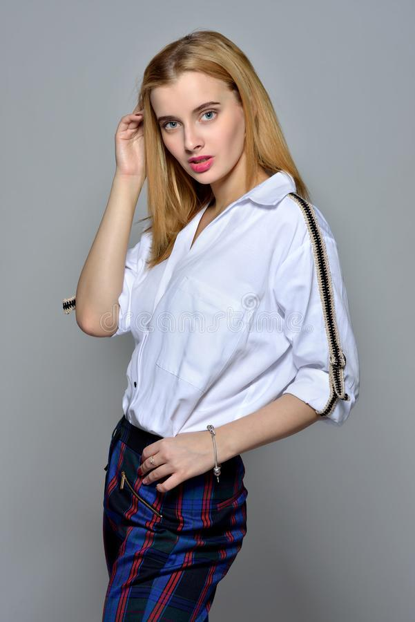 Beautiful blonde woman in white shirt and checked trousers. Torso portrait of the beautiful blonde woman in white shirt and  checked trousers stock image