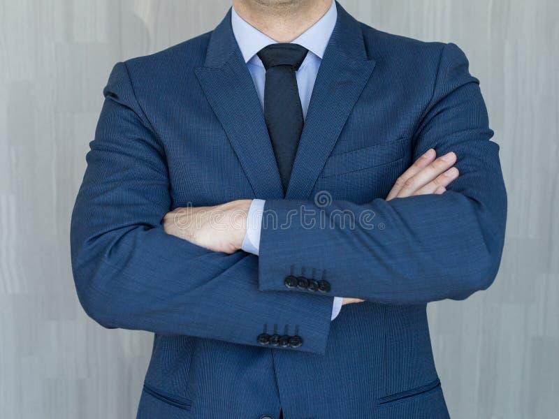 Torso van een zakenman die zich met gevouwen wapens in een klassiek marineblauw kostuum bevinden royalty-vrije stock afbeeldingen