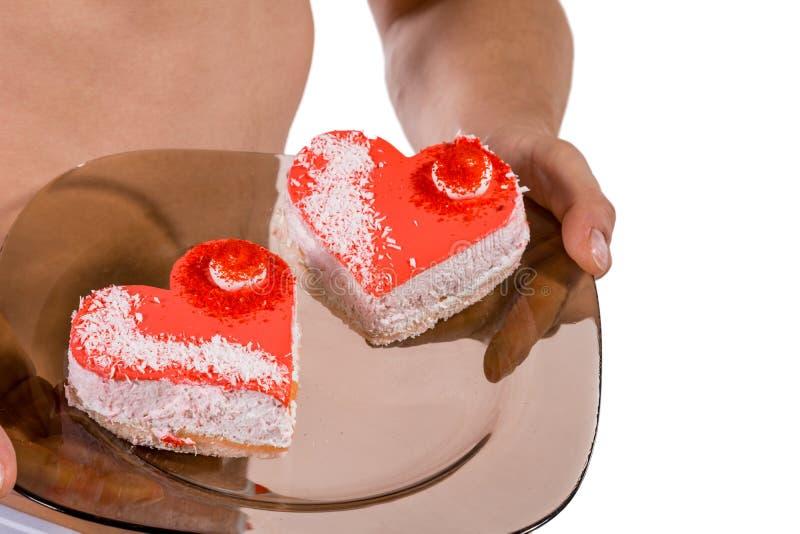 Torso van jonge knappe kerel met twee hart-vormige cakes op een plaat Sexy portret van de romantische mens met valentijnskaart  royalty-vrije stock foto's