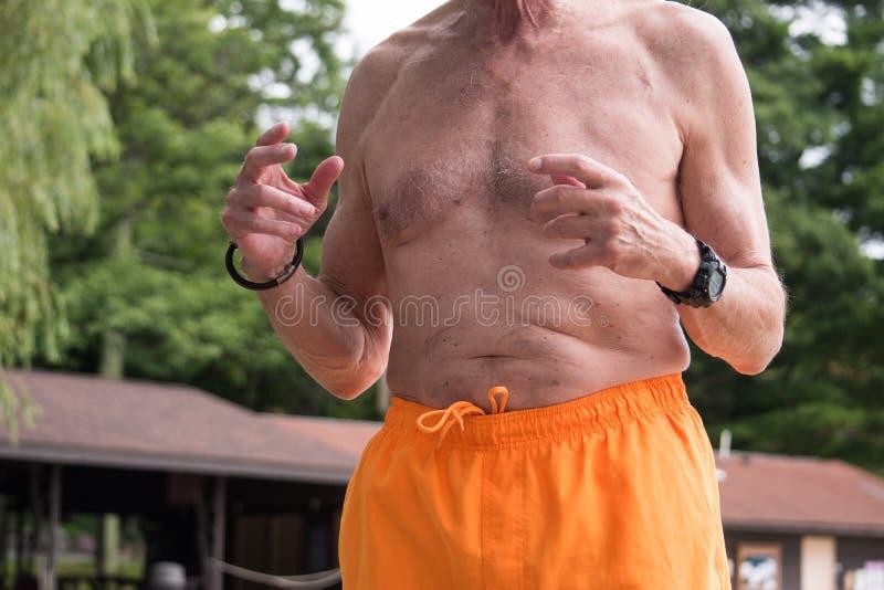 Torsomening van oudere mensen naakte chested in gele badpakslijtage stock afbeelding