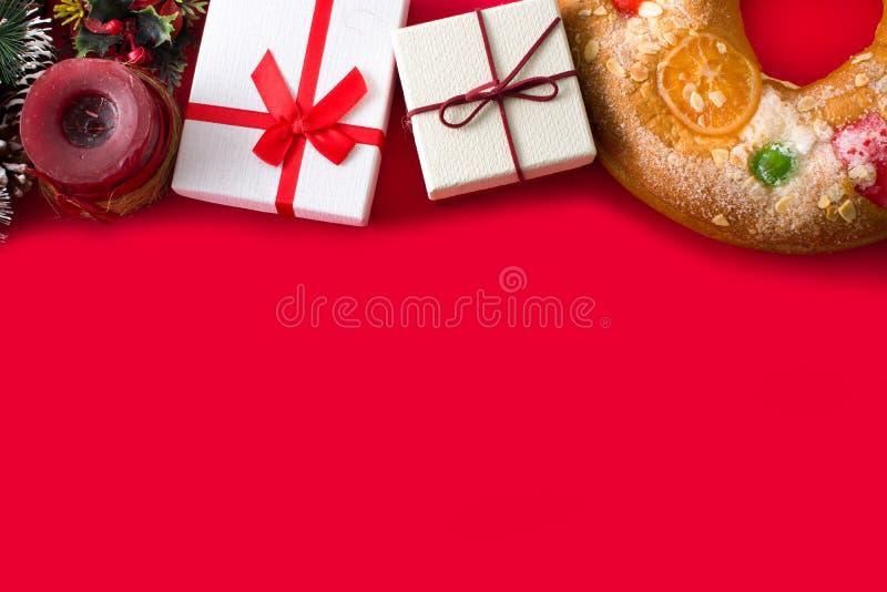 Torta 'Roscon de Reyes de la epifanía y fuentes de la Navidad en fondo rojo imagen de archivo libre de regalías