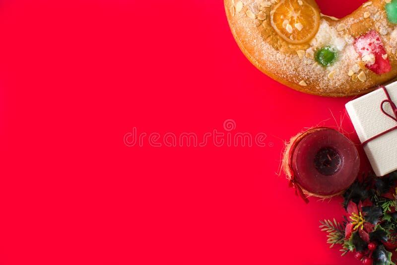 Torta 'Roscon de Reyes de la epifanía y fuentes de la Navidad en fondo rojo fotografía de archivo libre de regalías