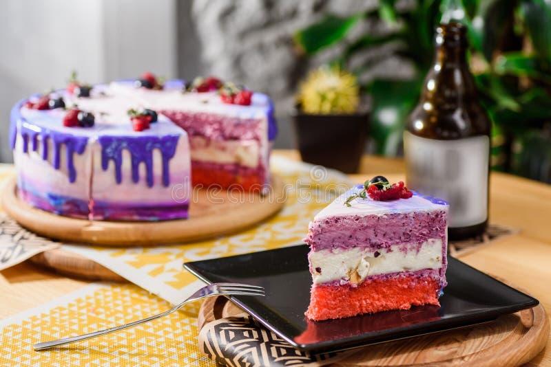 Torta acodada hermosa de la baya con una capa púrpura, blanca y rosada, adornada con las frambuesas y los arándanos en el top foto de archivo libre de regalías