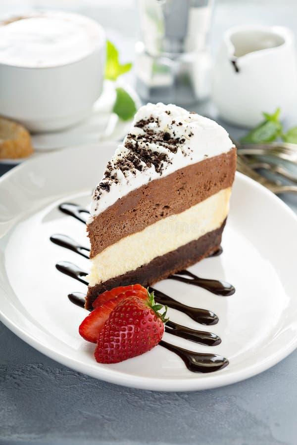 Torta acodada tres chocolates de la crema batida foto de archivo