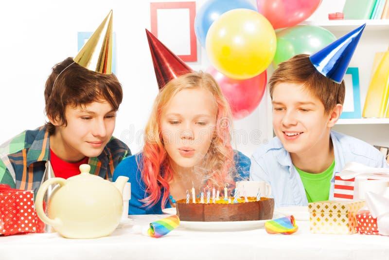 Torta adolescente hermosa del soplo de la muchacha en fiesta de cumpleaños fotos de archivo libres de regalías