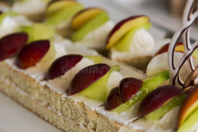 Torta adornada con la crema, rebanada de uvas, en una placa blanca Foco selectivo imagen de archivo libre de regalías