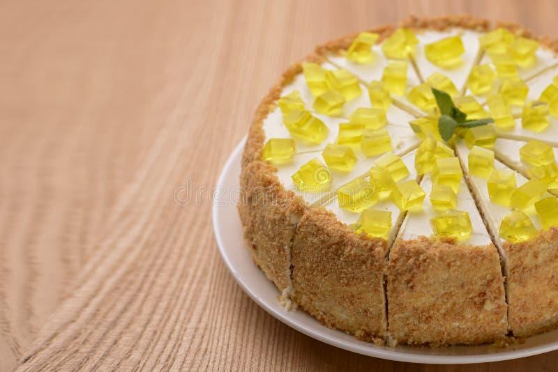 Torta al limone a più strati decorata con gelatina di citron e menta servita su piastra bianca su fondo di legno fotografia stock libera da diritti
