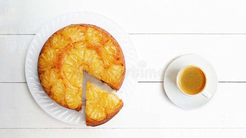 Torta al revés de la piña y taza de café en la etiqueta de madera blanca fotos de archivo