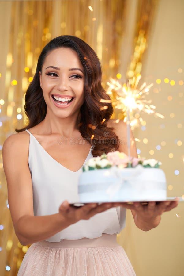 Torta alegre de la tenencia de la muchacha mientras que celebra a la persona del cumpleaños foto de archivo libre de regalías