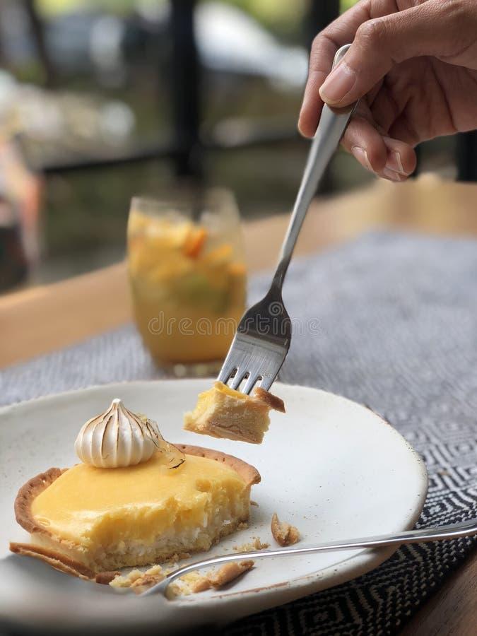 Torta amarilla del limón con la mano de la mujer foto de archivo libre de regalías