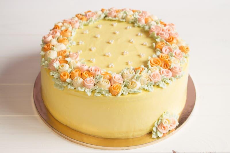 Torta amarillo claro de la crema batida con las flores poner crema en colores pastel fotografía de archivo libre de regalías