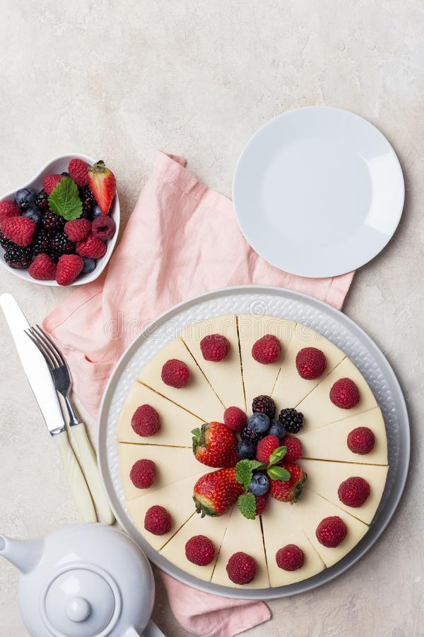 Torta ascendente cercana del día de fiesta con las bayas, la placa, la bifurcación y el cuchillo en el fondo blanco foto de archivo