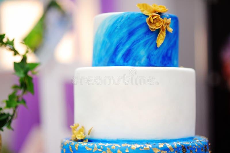 Torta azul elegante con las flores de oro en el banquete de boda fotografía de archivo libre de regalías