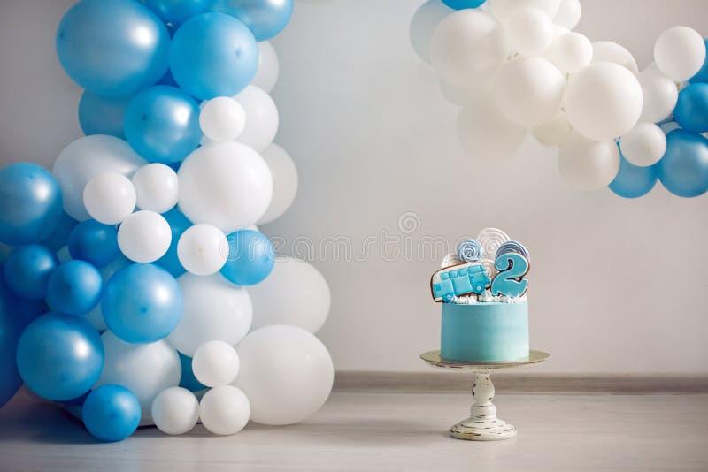 Torta azul en el cumpleaños de los niños con el número dos y el coche foto de archivo libre de regalías