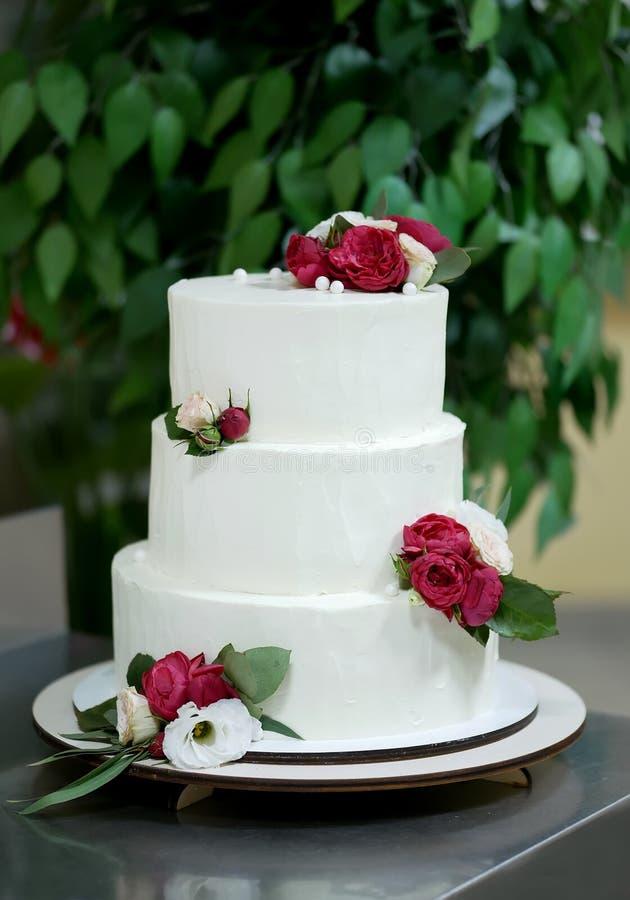 Torta blanca que se casa hermosa con las flores rojas fotos de archivo
