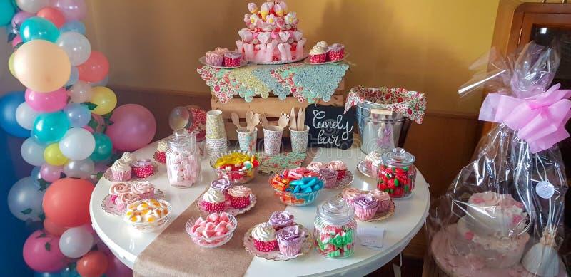 Torta, caramelos, melcochas, cakepops, frutas y otros dulces en la tabla del postre en la fiesta de cumpleaños de los niños fotos de archivo libres de regalías