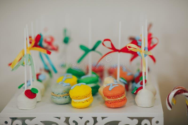Torta, caramelos, melcochas, frutas y otros dulces en la tabla del postre en la fiesta de cumpleaños de los niños foto de archivo libre de regalías