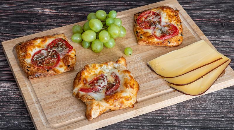 Torta caseiro com tomates e mentira do queijo em uma placa de madeira ao lado das uvas e das partes de queijo imagens de stock