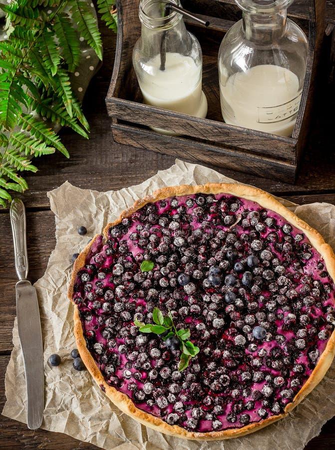 Torta caseiro com uva-do-monte e leite na tabela de madeira escura fotos de stock