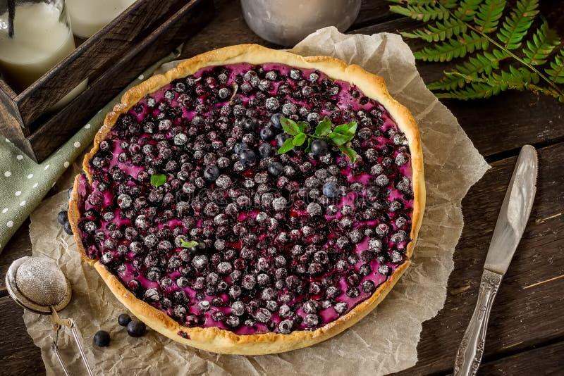 Torta caseiro com uva-do-monte e leite na tabela de madeira escura imagens de stock