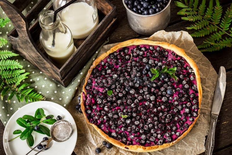 Torta caseiro com uva-do-monte e leite na tabela de madeira escura imagens de stock royalty free