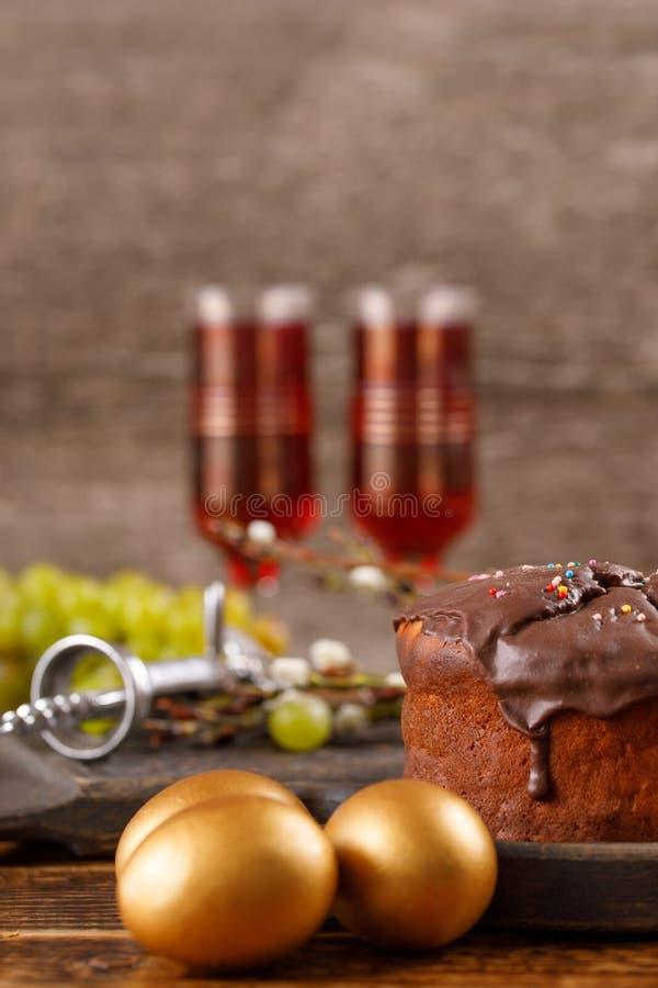 Torta casera fresca de Pascua, huevos de oro, vino rojo en vidrios del vintage, uvas y sacacorchos antiguo en la tabla Aún vida h imagenes de archivo
