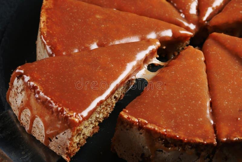 Torta com fim do caramelo acima no fundo escuro bolo com banana e caramelo fotografia de stock
