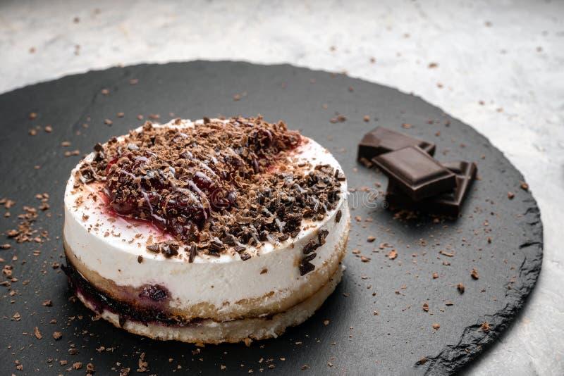 Torta con crema batida y atasco cerca de los pedazos de chocolate fotografía de archivo libre de regalías