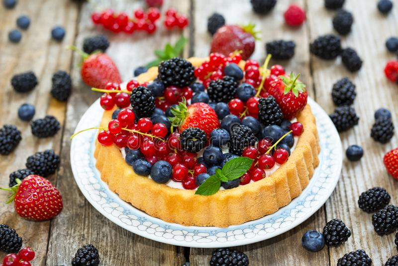 Torta con diversas bayas - fresas, arándanos, pasas, zarzamoras imagenes de archivo