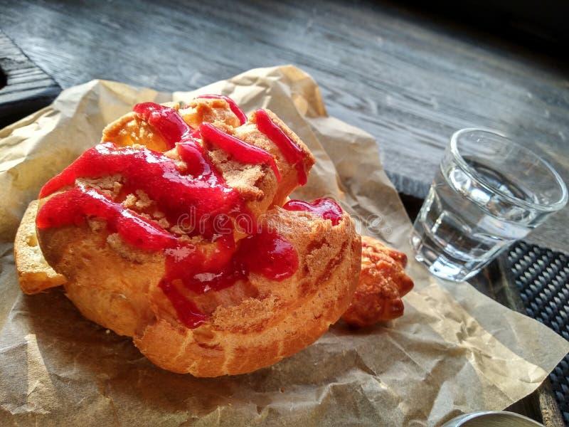 Torta con el atasco rojo torta de las natillas con el vidrio de agua tiempo soleado fotografía de archivo libre de regalías